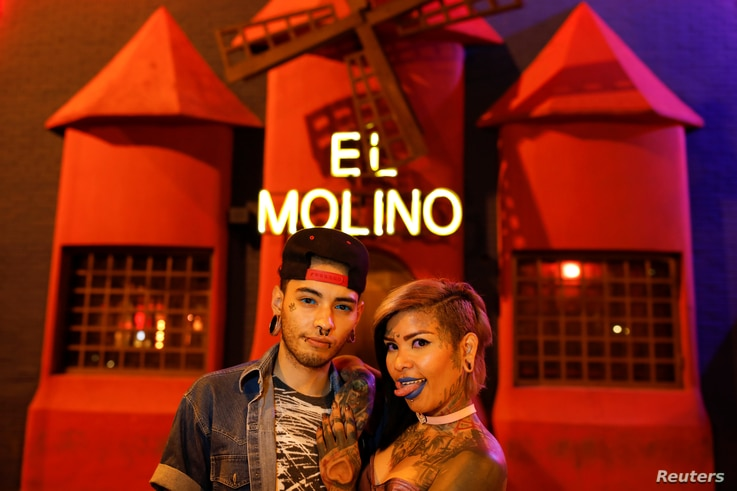 Tattoo artists, Kathriel Zambrano (L), 23, and Yohanna Gonzalez, 28, pose for a portrait in front of the bar El Molino where they first met, in Caracas, Venezuela, February 9, 2018.