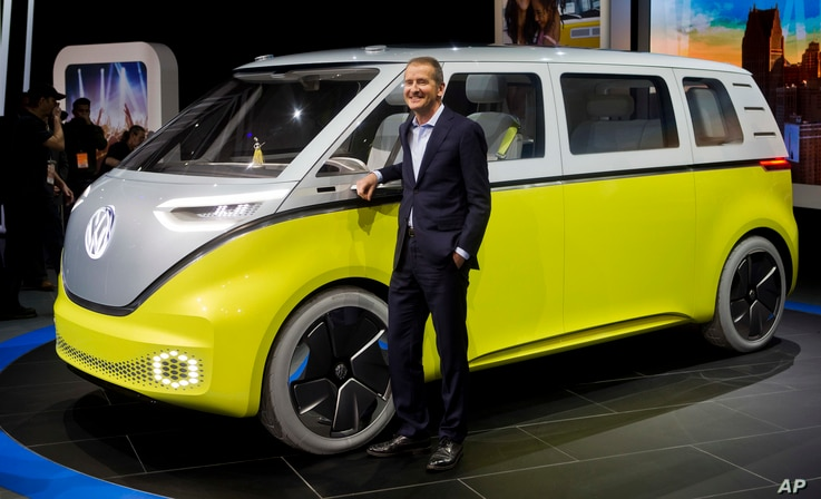 Dr. Herbert Diess, chairman of the VW brand, poses with the I.D. Buzz all-electric concept van at the North American International Auto Show, Jan. 9, 2017, in Detroit.