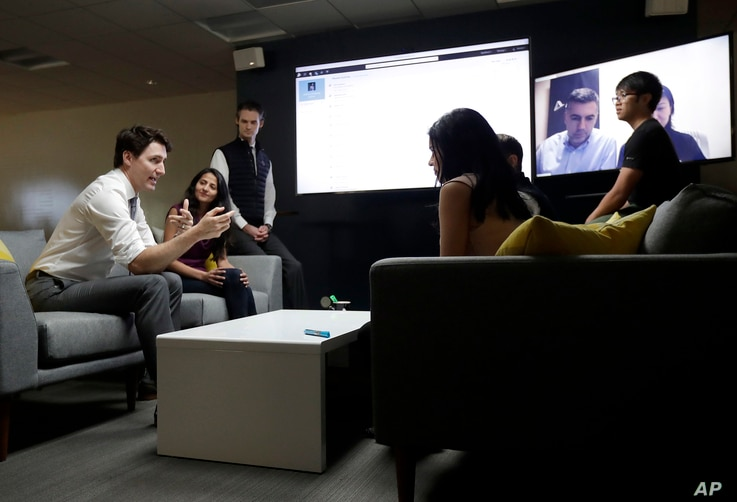 Canada's Prime Minister Justin Trudeau, left, speaks with AppDirect employees at their office in San Francisco, Feb. 8, 2018.