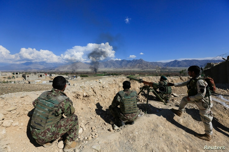 FILE - Afghan security forces take position during a gun battle between Taliban and Afghan security forces in Laghman province, Afghanistan, March 1, 2017.