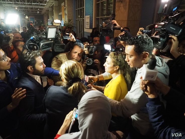 Media interviews an Egyptair host who has just arrived from the hijacked flight at Cairo airport, Tuesday, March 28, 2016. (H. Elrasam/VOA)