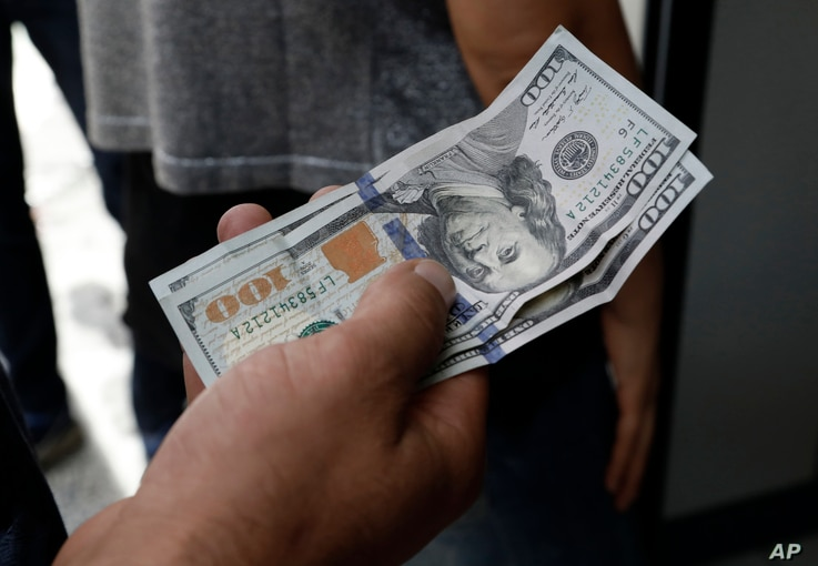 A Turkish man waits to change his U.S. dollars with Turkish liras inside a currency exchange shop in Ankara, Aug. 10, 2018. A financial shockwave ripped through Turkey on Friday as its currency nosedived on concerns about its economic policies and a ...