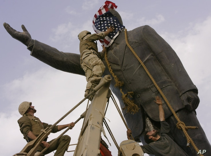 FILE - An Iraqi man, bottom right, watches Cpl. Edward Chin of the 3rd Battalion, 4th Marines Regiment, cover the face of a statue of Saddam Hussein with an American flag before toppling the statue in downtown in Baghdad, Iraq, April 9, 2003.