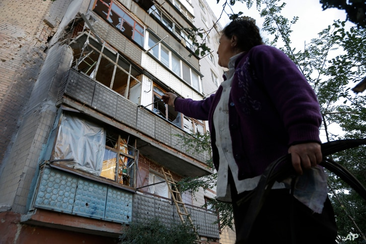 A woman points to a damaged building after shelling in the city of Slovyansk, Donetsk region, eastern Ukraine, June 29, 2014.