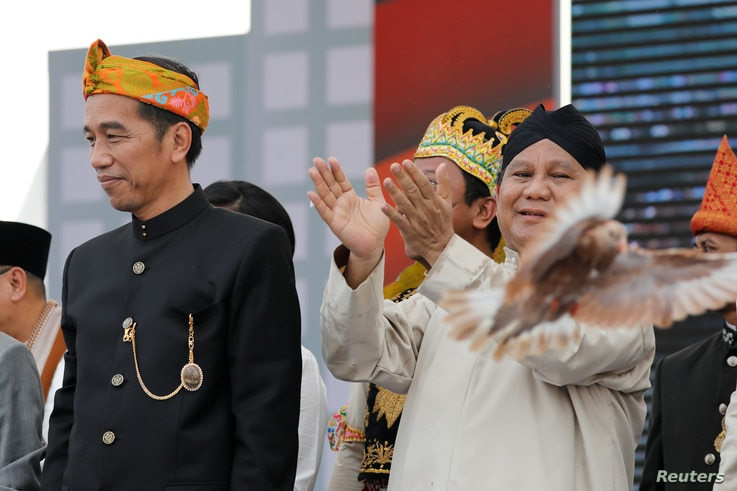 FILE - A freshly released dove is seen near presidential challenger Prabowo Subianto, right, as Indonesian Pesident Indonesian President Joko Widodo looks on during a ceremony marking the start of the campaigning period for next year's presidential e...