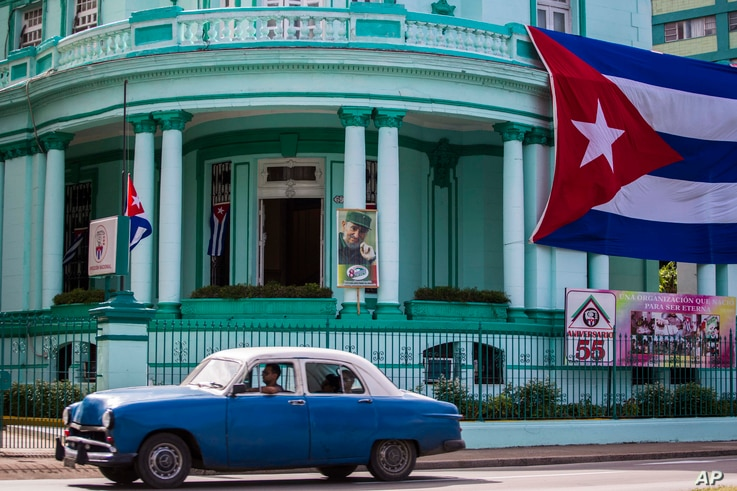 A Cuban flag flies at half-staff, left, and a picture of Fidel Castro decorates the headquarters of the Committees for the Defense of the Revolution one day after Castro died in Havana, Cuba, Nov. 26, 2016.