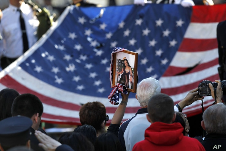 The World Trade Center Flag is presented as friends and relatives of the victims of the September 11, 2001, terrorist attacks, the National September 11 Memorial at the World Trade Center site in New York, September 11, 2012.