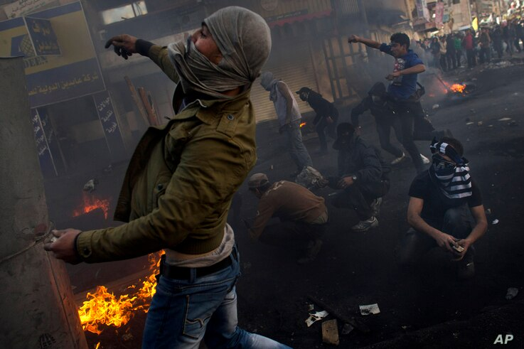 Palestinians clash with Israeli forces, not pictured, in the West Bank city of Hebron, April 4, 2013.