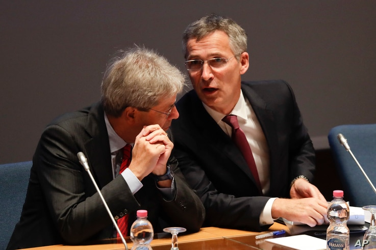 """FILE - Italian Foreign Minister Paolo Gentiloni, left, and NATO Secretary General Jens Stoltenberg during """"Nato cooperation with Partners in the Mediterranean and Middle East"""" meeting at the NATO Defense College headquarters, in Rome, Oct. 14, 2016."""