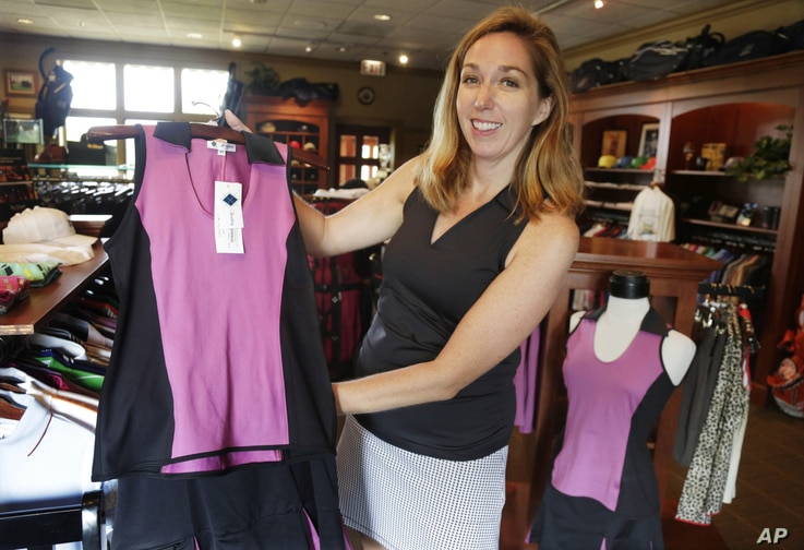 FILE -  Kelly Daugherty, co-owner of Smashing Golf & Tennis, poses for a photo with her clothing line in the pro shop at Biltmore Country Club in North Barrington, Ill., Aug. 20, 2013.