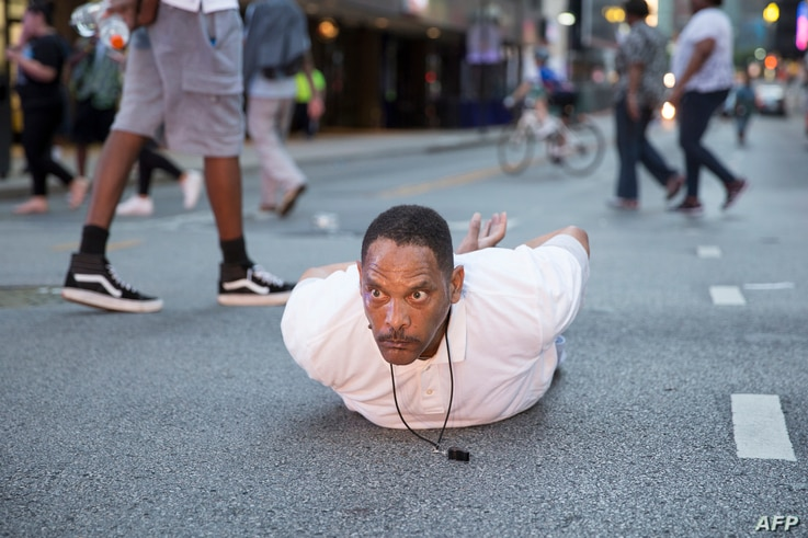 """A man lays on the ground after yelling """"Don't shoot me"""" at police during a rally in Dallas, Texas, on Thursday, July 7, 2016 to protest the deaths of Alton Sterling and Philando Castile."""