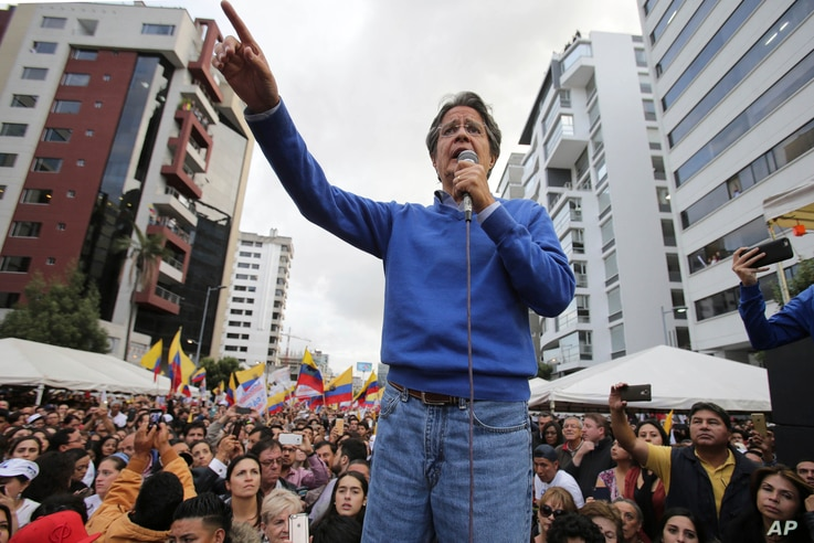 Presidential candidate Guillermo Lasso speaks during a rally outside the National Electoral Council in Quito, Ecuador, Monday, April 3, 2017.