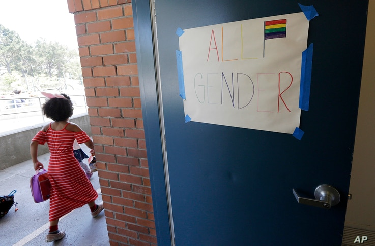 FILE - A camper walks past a sign for an all gender bathroom at the Bay Area Rainbow Day Camp in El Cerrito, Calif., July 11, 2017.