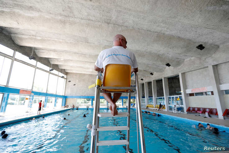 A lifeguard watches over swimmers at the Marville indoor swimming pool which is part of the Marville sports complex, in Saint-Denis, France, July 21, 2017.
