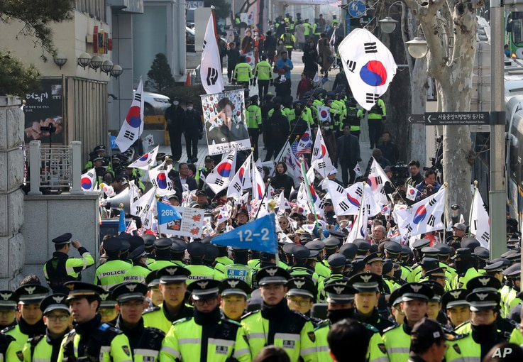 """Supporters of South Korean ousted President Park Geun-hye wave national flags and picture of Park outside of a prosecutors' office in Seoul, South Korea, March 21, 2017. Park said she was """"sorry"""" to the people as she arrived Tuesday at a prosecutors'..."""
