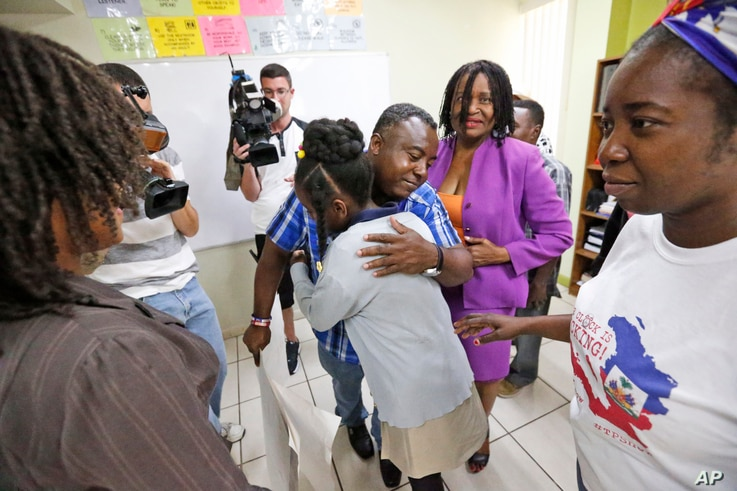 FILE - Pierrot Mervilier, center rear, hugs a girl that did not wish to be identified, living in the U.S. with Temporary Protected Status (TPS) after she and her family spoke to members of the media.