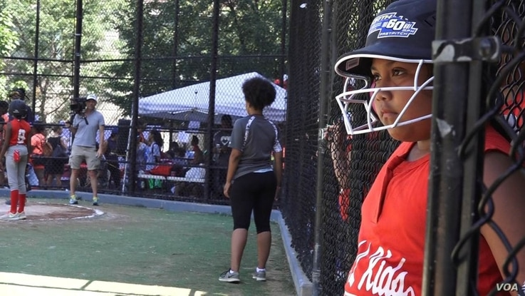 A young softball player on the South Bronx Red Wings awaits her turn at the dugout at the Harlem RBI field, in New York, Aug. 12, 2016.