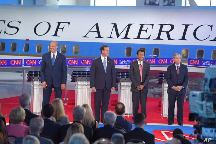 Republican presidential candidates, former New York Gov. George Pataki, left, former Pennsylvania Sen. Rick Santorum, second from left, Louisiana Gov. Bobby Jindal, second from right, and Sen. Lindsey Graham, R-S.C., take the stage in the early CNN R...