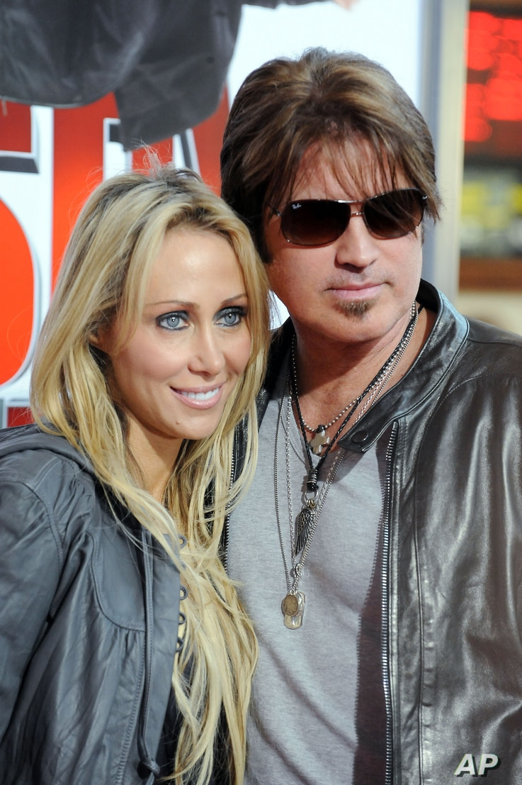 "FILE - In this Jan. 9, 2010 file photo, Billy Ray Cyrus, at right, and his wife Laeticia ""Tish"" Cyrus, arrive to the premiere of ""The Spy Next Door"" in Los Angeles."