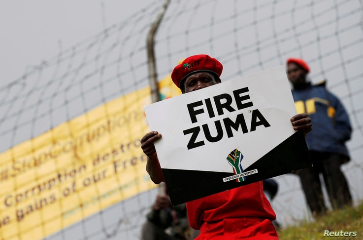FILE - Supporters of various opposition parties hold placards calling for the removal of President Jacob Zuma outside the Constitutional Court in Johannesburg, South Africa, May 15, 2017.