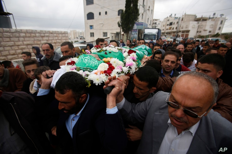 FILE - Palestinians chant slogans as they carry the body of Abdel-Fattah al-Sharif, during his funeral, in the West Bank city of Hebron, May 28, 2016.