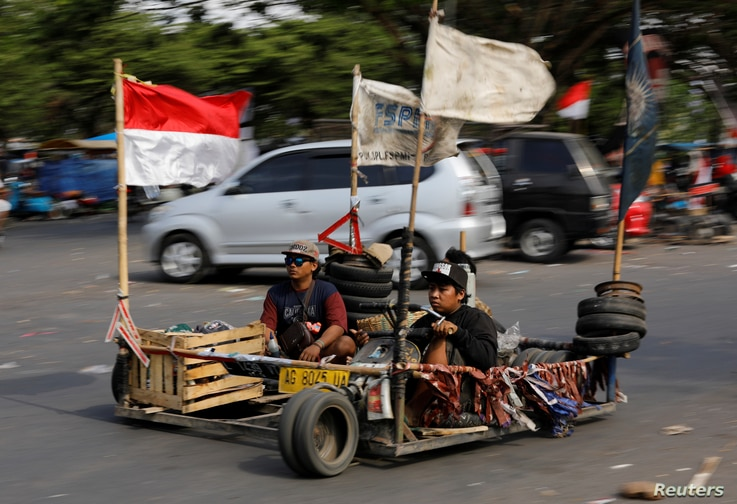 FILE - Extreme Vespa enthusiasts drive near the site of a weekend scooter festival in Kediri, East Java, Indonesia, Aug. 5, 2018.
