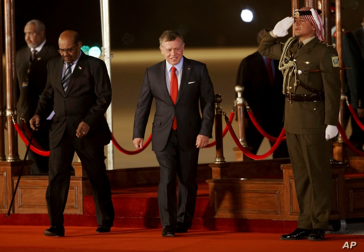 Jordan's King Abdullah II, center, greets Sudan's President Omar al-Bashir, left, upon his arrival at Queen Alia International Airport in Amman, Jordan, March 28, 2017. Bashir is among 21 Arab leaders gathering for a summit.
