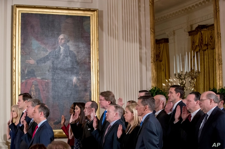 FILE - From left, President Donald Trump's advisors Kellyanne Conway, Jared Kushner, Steve Bannon, and Trump Chief of Staff Reince Priebus, and other members of White House senior staff are sworn in at the White House, in Washington, Jan. 22, 2017.