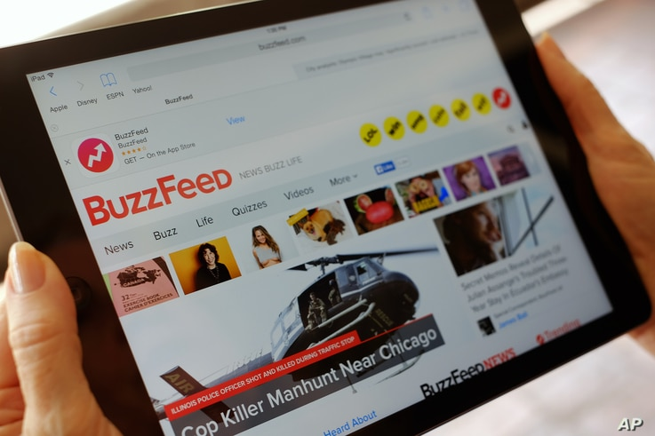 FILE - The BuzzFeed website is displayed on an iPad held by an Associated Press staffer in Los Angeles, Sept. 1, 2015.
