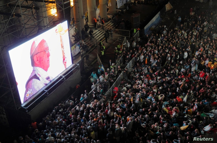 Faithful watch the inaugural mass of Pope Francis on a giant screen next to the Metropolitan Cathedral in Buenos Aires, Mar. 19, 2013.