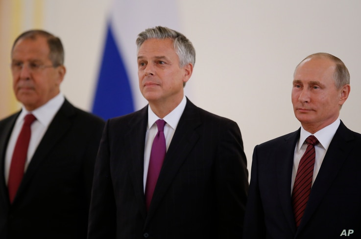 Russian President Vladimir Putin, right, smiles receiving credentials from the U.S. Ambassador, Jon Huntsman, center, during a ceremony in the Kremlin in Moscow, Russia, on Tuesday, Oct. 3, 2017.