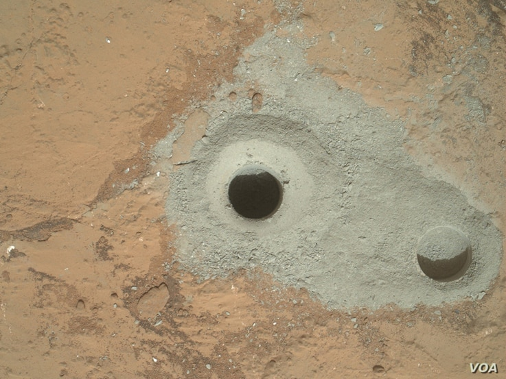 """At the center of this image from NASA's Curiosity rover is the hole in a rock called """"John Klein"""" where the rover conducted its first sample drilling on Mars."""