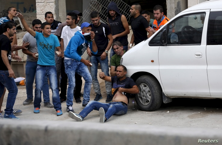 Palestinians try to evacuate a wounded man during clashes with Israeli troops at Qalandia checkpoint near occupied West Bank city of Ramallah October 6, 2015. Palestinian President Mahmoud Abbas said on Tuesday he did not want a spike in deadly viole...