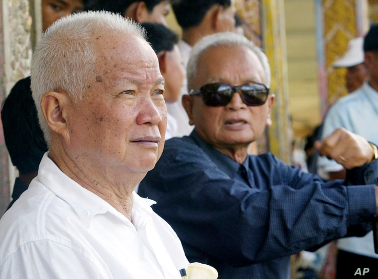 FILE - Former Khmer Rouge leaders Khieu Samphan, left, and Nuon Chea sit together during funeral services for Khieu Ponnary, the first wife of Khmer Rouge leader Pol Pot, in the former Khmer Rouge stronghold of Pailin, northwestern Cambodia, July 3, ...