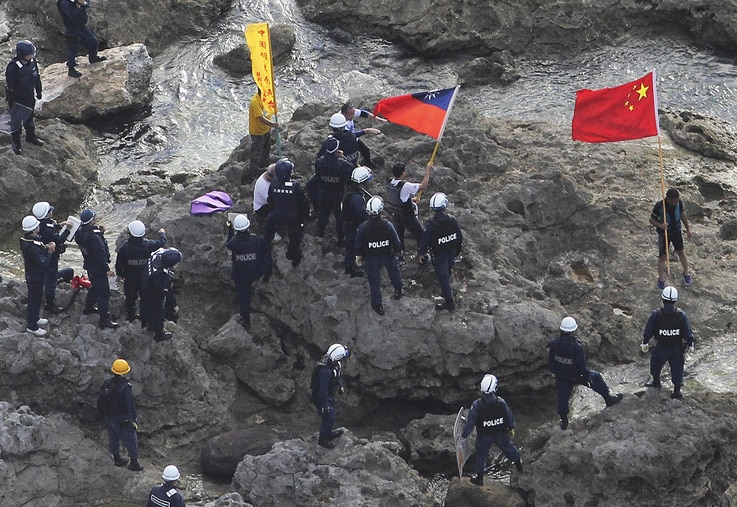 August 15, 2012: Activists holding Chinese and Taiwanese flags are arrested by Japanese police officers after landing on Uotsuri Island, one of the islands of Senkaku in Japanese and Diaoyu in Chinese, in East China Sea.