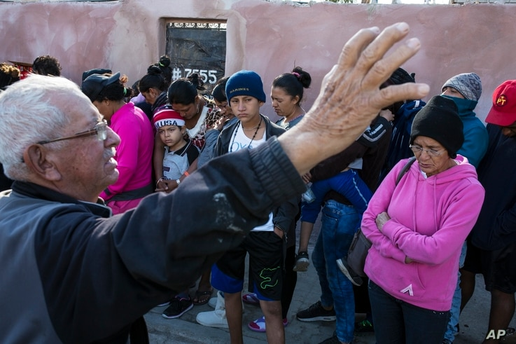 "A volunteer who helped with the delivery of a donated breakfast prays as Central American migrants wait in a line to receive the breakfast at a temporary shelter in Tijuana, Mexico, Nov. 17, 2018.  The mayor has called the migrants' arrival an ""avala..."