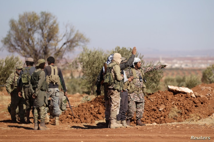 FILE - Rebel fighters gather during their advance towards the Islamic State-held city of al-Bab, northern Syria Oct. 26, 2016.