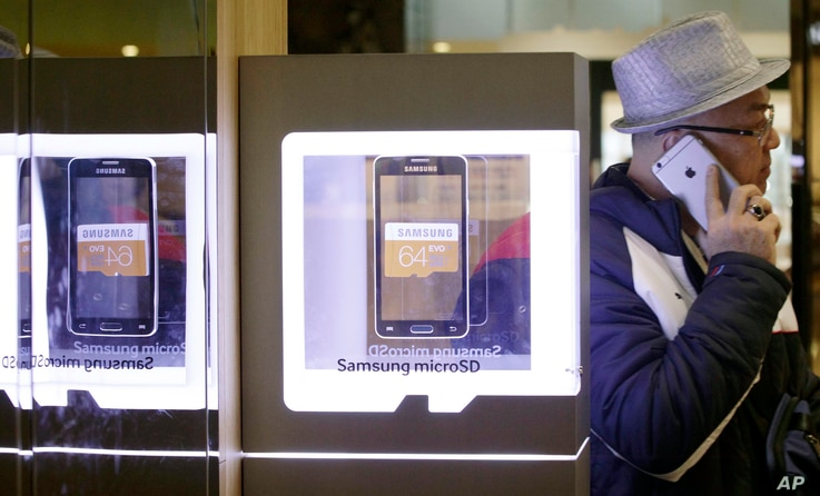 FILE - A man uses an Apple iPhone as he passes a Samsung shop in Seoul, South Korea, Jan. 29, 2015.