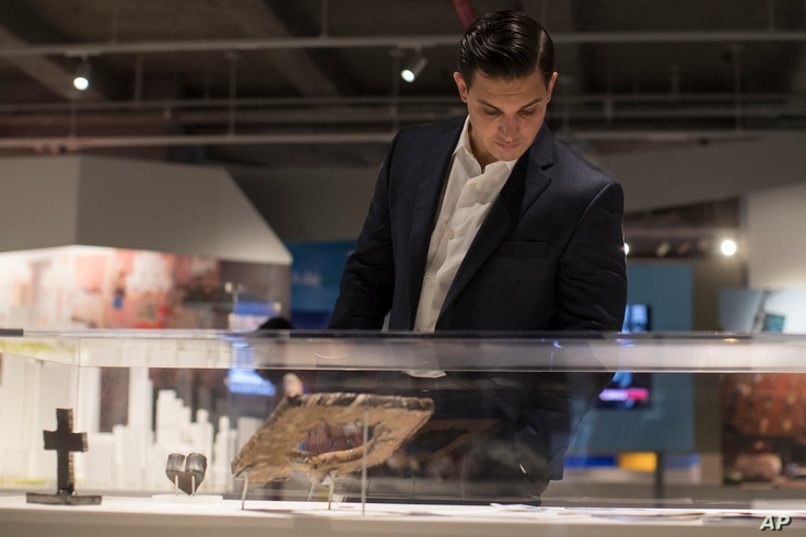 A visitor to a preview of the 9/11 Tribute Museum in New York looks a display with artifacts from the World Trade Center site, June 8, 2017.