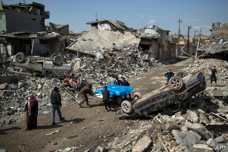 Residents of western Mosul, Iraq, carry the bodies of several people killed during fighting between Iraq security forces and Islamic State, March 24, 2017. Residents of Mosul's Jidideh neighborhood say that scores of people were killed by airstrikes ...