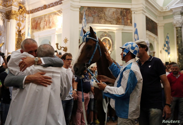The captain of the Onda parish, Alessandro Toscano, embraces the priest at the church before the Palio di Siena horse race in Siena, Italy, July 2, 2017.
