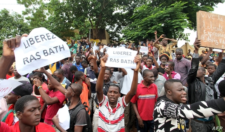 """FILE - People hold placards reading """"Free Rasbath"""", a young radio presenter Mohamed Youssouf Bathily also known as """"Rasbath"""" who was arrested, as they take part in a demonstration in front of Bamako's court, Aug. 17, 2016."""