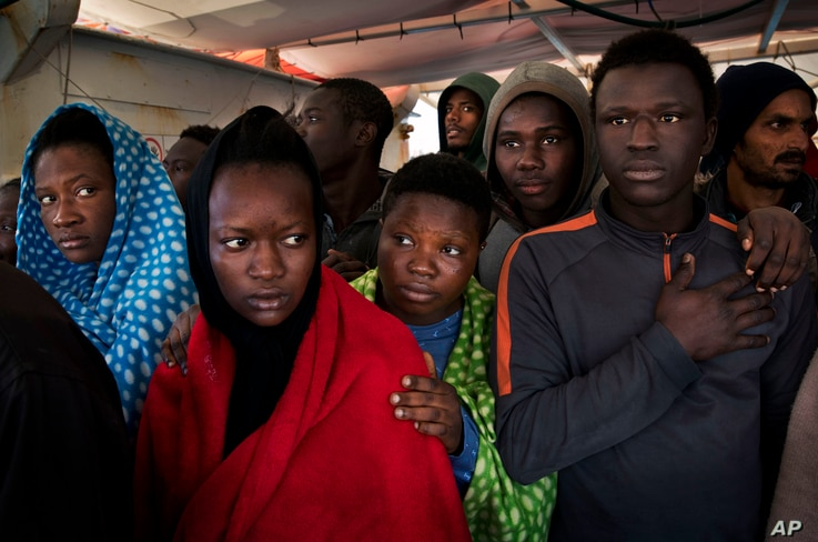 Migrants aboard the Golfo Azurro rescue vessel wait to be transferred to Italian authorities in Trapani harbor, on the Italian island of Sicily, Saturday, April 8, 2017.