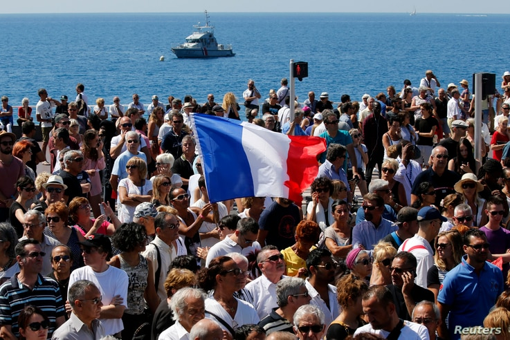 A French flag flies among the crowd as people gather in front of the Monument du Centenaire during a minute of silence on the third day of national mourning to pay tribute to victims of the truck attack along the Promenade des Anglais on Bastille Day...