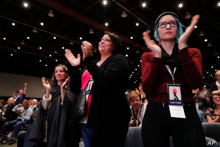 Women applaud while listening to actress Rose McGowan speak at the inaugural Women's Convention in Detroit, Oct. 27, 2017. McGowan recently went public with her allegation that film company co-founder Harvey Weinstein raped her.
