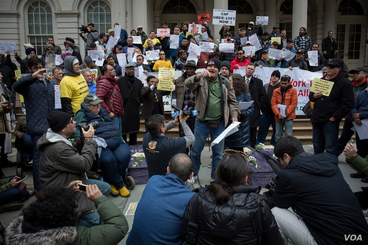 Romanian immigrant Nicolae Hent, a taxi driver and friend of Nicanor Ochisor, addresses a crowd of taxi drivers and media from the steps of New York's City Hall. (R. Taylor/VOA)