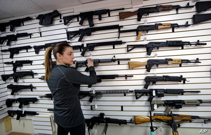 Gun shop owner Tiffany Teasdale-Causer returns a Ruger AR-15 semi-automatic rifle, the same model, though in gray rather than black, used by the shooter in a Texas church massacre two days earlier, to it's place on a wall with dozens of other semi-au...