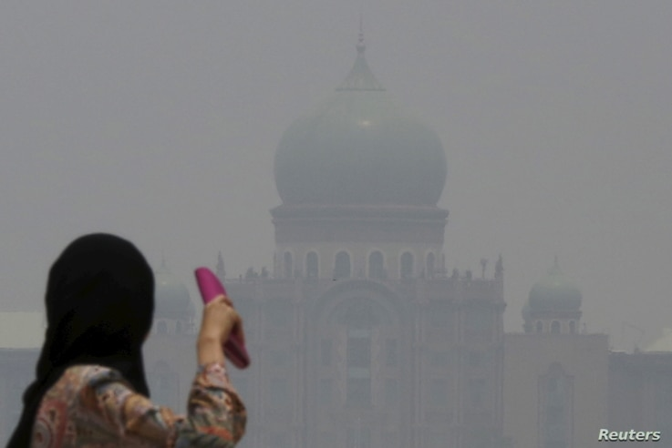 A woman looks toward the Malaysian prime minister's office in Putrajaya, which is shrouded in haze from fires in Indonesia, Oct. 6, 2015.