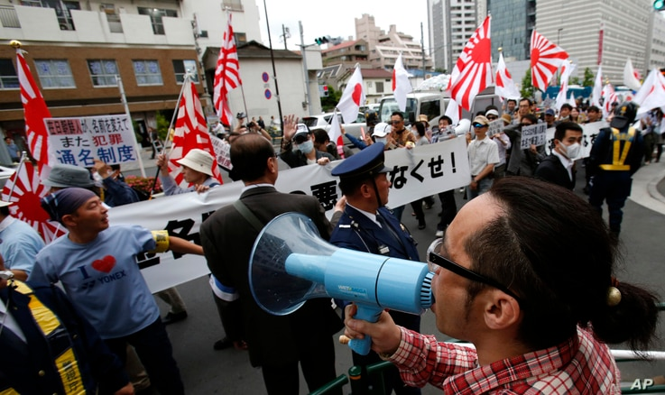 """FILE - Nationalist protesters, at rear, march through a Tokyo street to denounce """"privileges"""" for Koreans living in Japan, past a counterprotester, bottom right, who yells at them. Extremist groups sometimes take to Tokyo streets, waving militarist r..."""