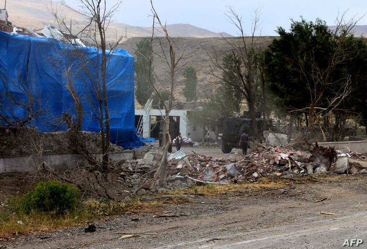 Wreckage lies on the ground in front of a Turkish military station covered by a tarpaulin after a suicide attack on August 2, 2015 in east Turkey town Dogubeyazit in Agri Province.